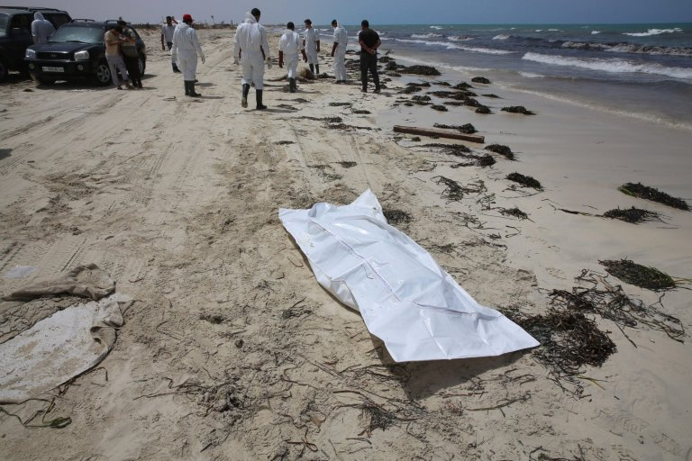 epa05343241 A body bag lies on the beach as rescue personnel work where bodies of migrants washed up, in Zuwarah, west of Tripoli, Libya, 02 June 2016. According to media reports citing Red Crescent officials, at least 85 bodies have washed up onto Libyan beaches this week.  EPA/MOHAME BEN KHALIFA ATTENTION EDITORS: GRAPHIC CONTENT