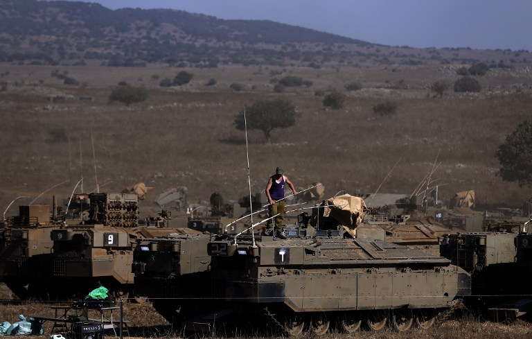 An Israeli soldier stands on top of an armoured personnel carrier stationed in the Israeli-annexed Golan Heights on August 21, 2015, after rockets fired from Syria to northern Israel. Israel launched artillery and air strikes against Syrian army positions in the Golan Heights on August 20 in response to rocket fire, military sources said. AFP PHOTO / AHMAD GHARABLI