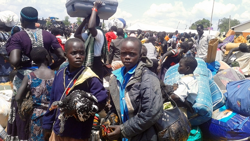 photo_eight_south_sudanese_children_carrying_thier_chicken_and_lagguage_at_elegu_collection_centre._unhcr_says_more_than_percent_of_the_refugees_are_children_and_women_1