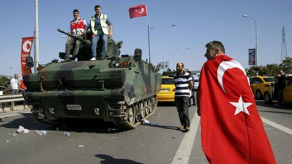 A man wrapped in a Turkish flag walks past a military vehicle in front of Sabiha Airport, in Istanbul, Turkey July 16, 2016. REUTERS/Baz Ratner