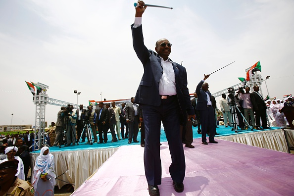Sudanese President Omar al-Bashir greets the audience during a ceremony in his honour upon his return in the country from Ethiopa on July 30, 2016 in the capital Khartoum. Omar al-Bashir was honoured during a ceremony after he received the African Dignity Award during the first African Dignity Forum launched by Addis Ababa University (AAU) in Addis Ababa. / AFP / ASHRAF SHAZLY        (Photo credit should read ASHRAF SHAZLY/AFP/Getty Images)