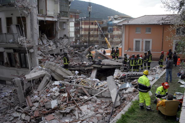 L'AQUILA, ITALY - APRIL 06:  Rescue workers search for trapped people on a damaged building after an earthquake on April 6, 2009 in L'Aquila, Italy. The 6.3 magnitude earthquake tore through central Italy, devastating historic mountain towns, killing at least 150 people and injuring 1500.  (Photo by Marco Di Lauro/Getty Images)