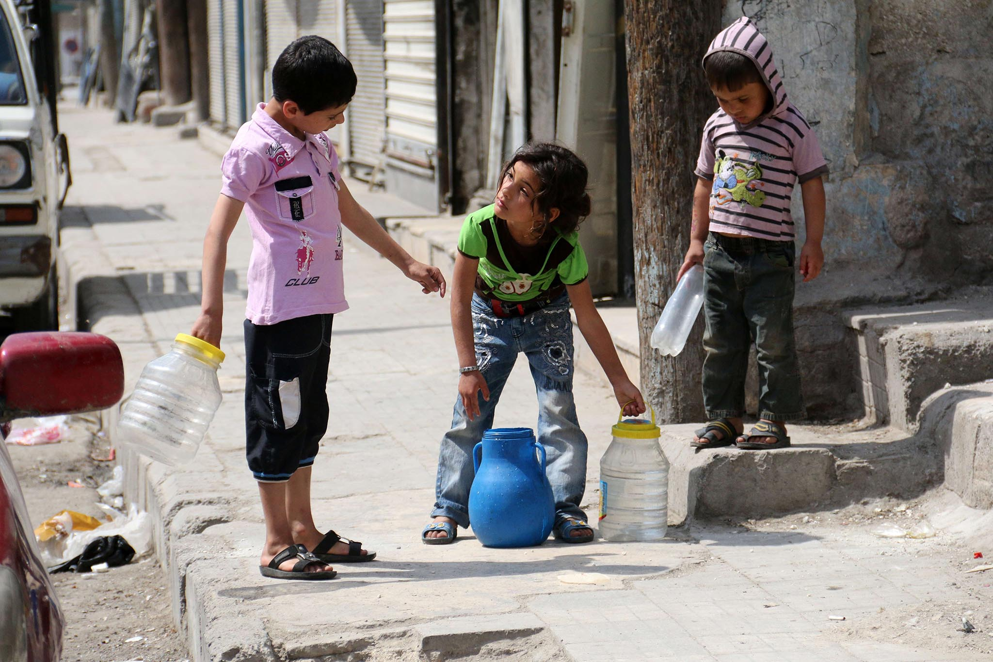 Children carry buckets of water in a rebel-held area in Aleppo on May 12, 2014. Residents of Syria's second city Aleppo have been without water for more than a week because jihadists have cut supplies into rebel and regime-held areas, the Syrian Observatory for Human Rights said on May 10. AFP PHOTO/ZEIN AL-RIFAIZEIN AL-RIFAI/AFP/Getty Images