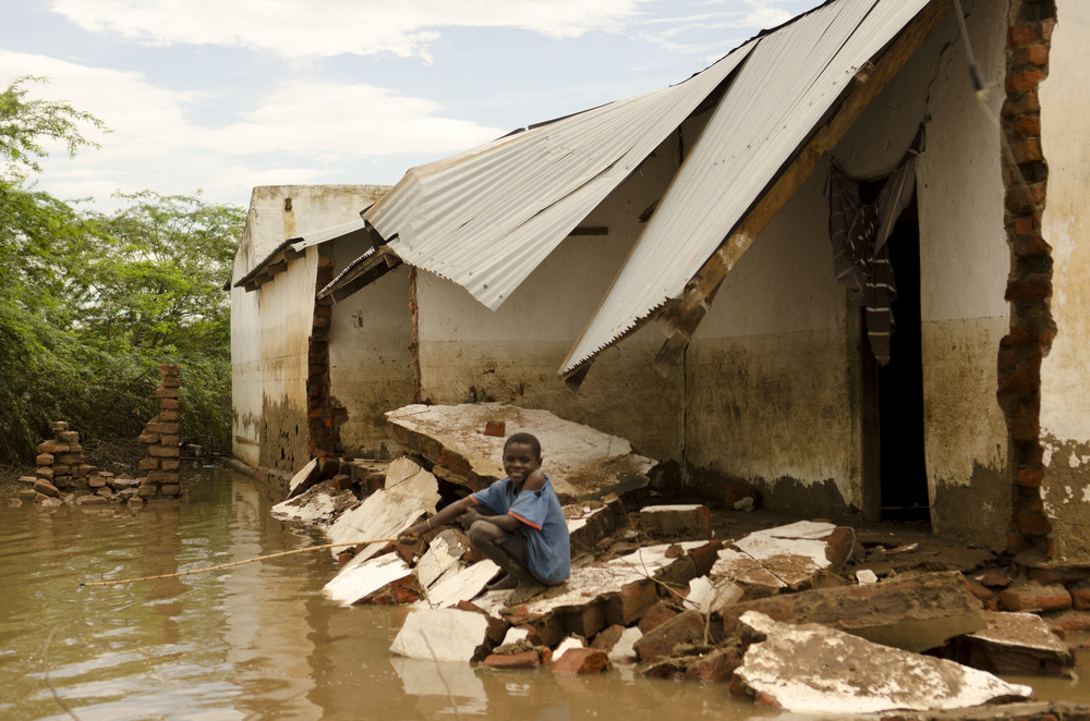Boy fishing in a house destroyed by floods. Bangula, Malawi