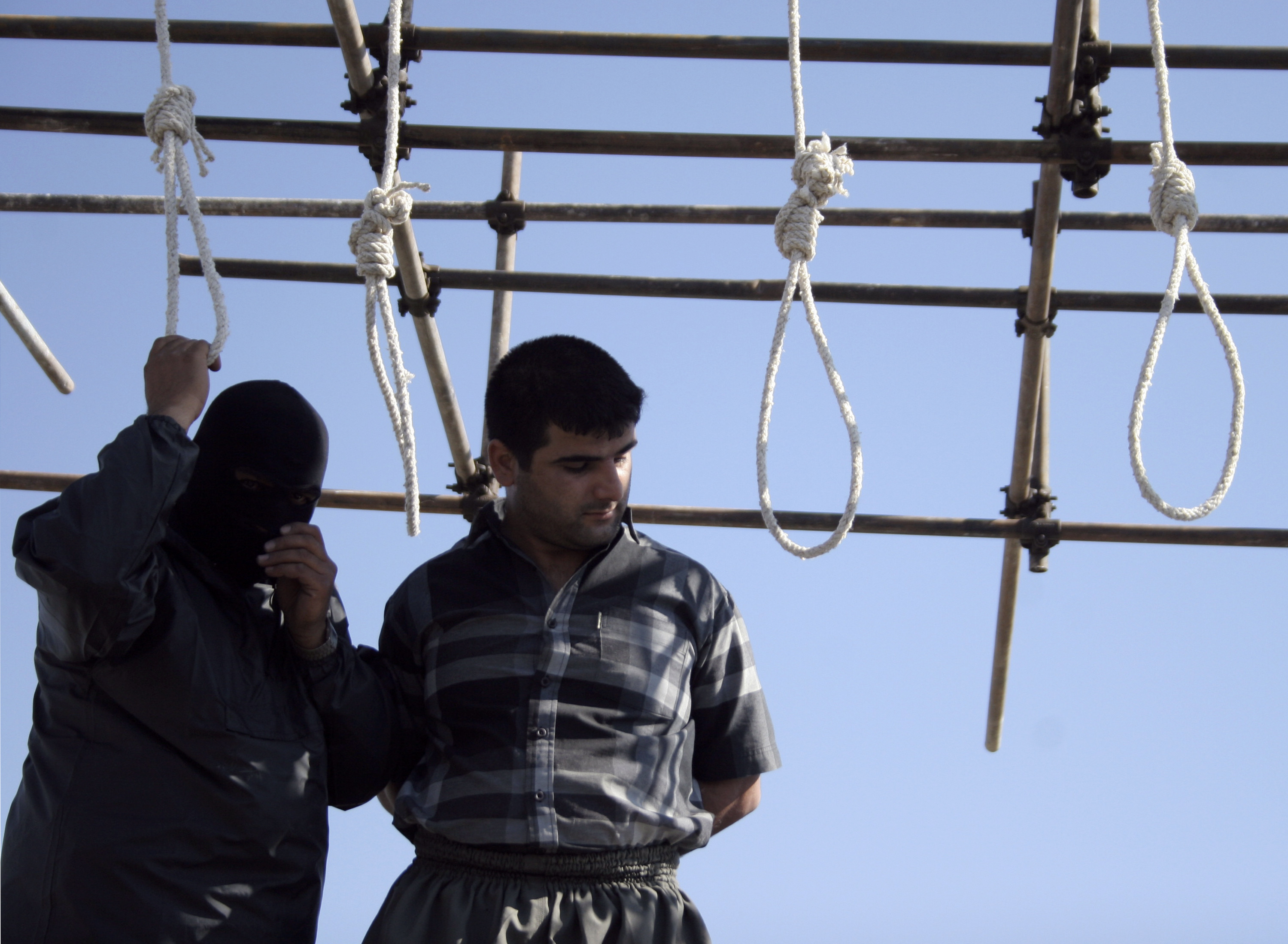 A policeman prepares a man, convicted of various charges, for his hanging in Mashhad, 924 km (574 miles) east of Tehran August 1, 2007. REUTERS/Stringer (IRAN) - RTR1SFLH