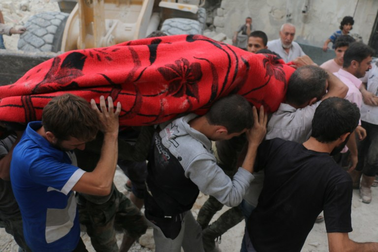 EDITORS NOTE: Graphic content / Syrians carry a body following bombardment on the al-Marja neighbourhood of the northern Syrian city of Aleppo on September 23, 2016.  Missiles rained down on rebel-held areas of Syria's Aleppo, causing widespread destruction that overwhelmed rescue teams, as the army prepared a ground offensive to retake the city.   / AFP PHOTO / AMEER ALHALBI