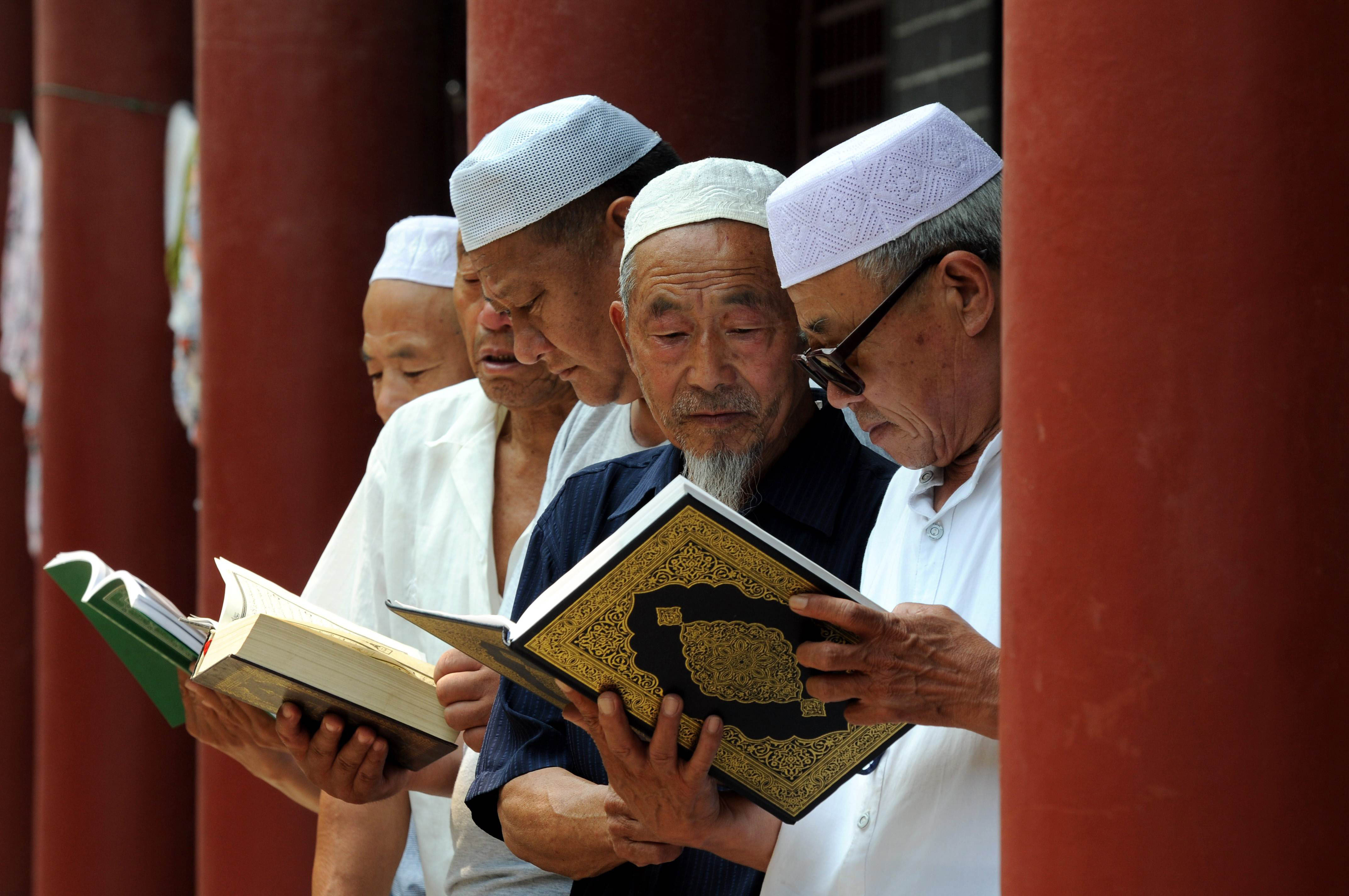 This picture taken on June 30, 2014 shows Chinese Muslims reading the Koran at a mosque in Tancheng, in eastern China's Shandong province, at the beginning of the holy month of Ramadan.  Across the Muslim world, the faithful fast from dawn to dusk, and abstain from eating, drinking, smoking and having sex during that time as they strive to be more pious and charitable.      CHINA OUT     AFP PHOTO