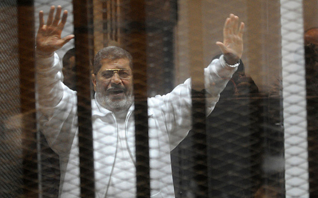 Egypt's deposed Islamist president Mohamed Morsi waves from inside the defendants cage during his trial at the police academy in Cairo on January 8, 2015. An Egyptian court is to deliver a verdict on April 21 in the trial of Morsi and 14 others charged with inciting the killing of protesters, judicial officials said. AFP PHOTO / STR        (Photo credit should read STR/AFP/Getty Images)