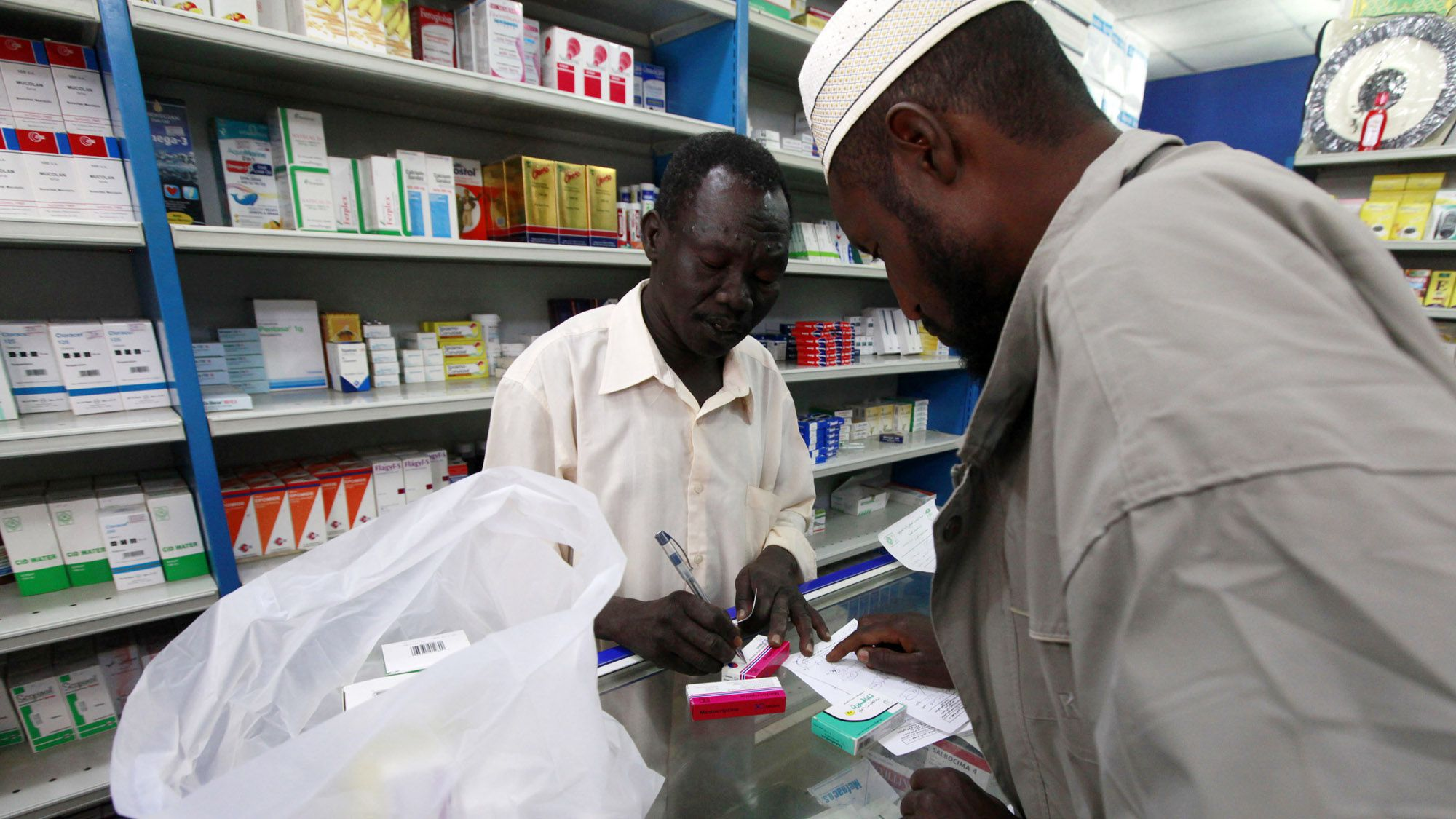 A customer buys medication at a pharmacy in Khartoum, January 24, 2012. Doing business has never been easy in Sudan, which suffers from a U.S. trade embargo, poverty, high inflation and the legacy of years of armed conflict. Even so the country, home to 32 million people and rich in oil, minerals such as gold and copper, and vast areas of farmland, has always attracted investors who do not mind taking some risks. But the investment climate has deteriorated further since South Sudan took away two-thirds of the country's oil production when it seceded in July.  Picture taken January 24, 2012. To match feature SUDAN-INVESTMENT   REUTERS/ Mohamed Nureldin Abdallah (SUDAN - Tags: BUSINESS POLITICS) - RTR2WU0T