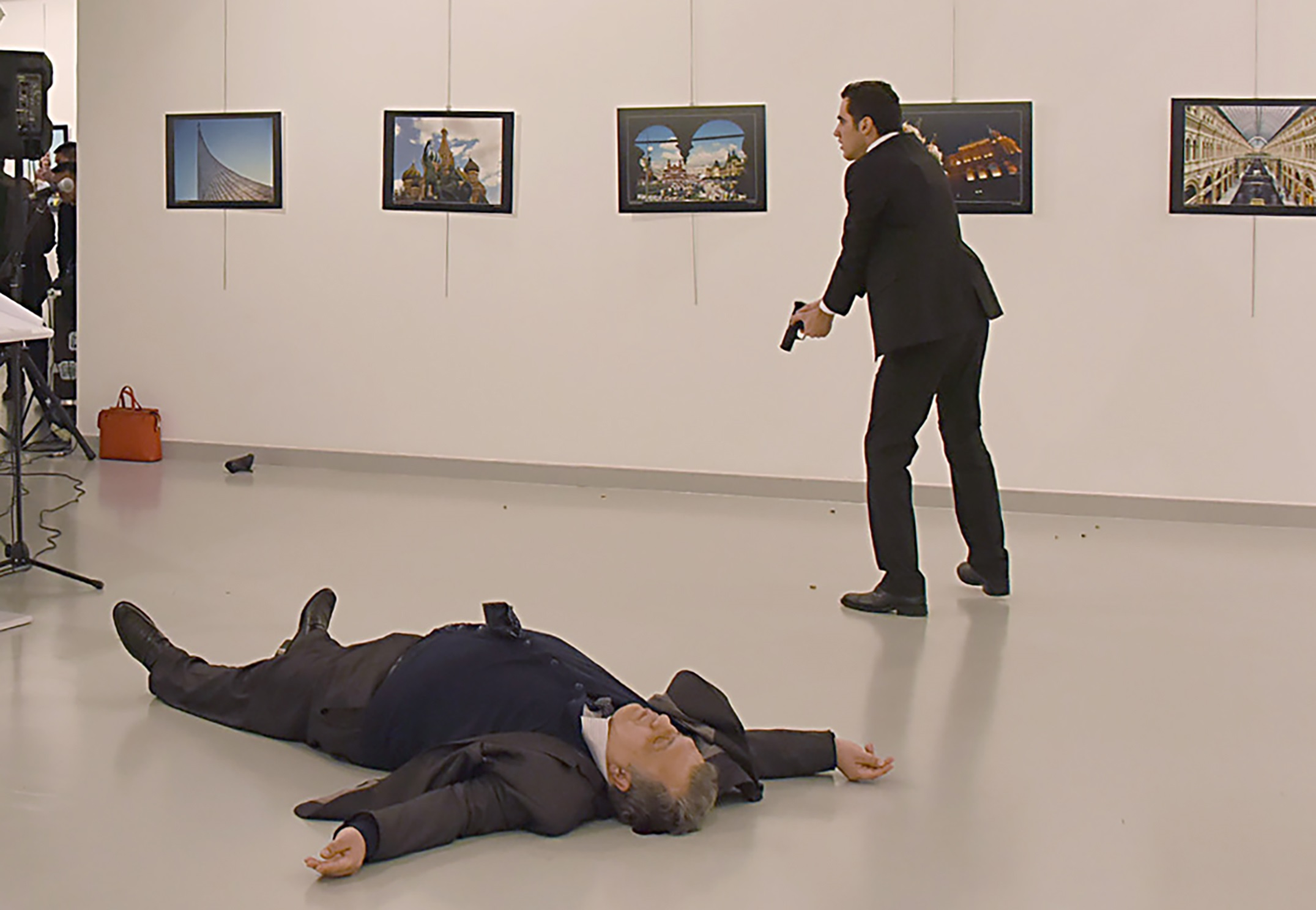 "This picture taken on December 19, 2016 shows Andrey Karlov (L), the Russian ambassador to Ankara, lying on the floor after being shot by a gunman (R) during an attack during a public event in Ankara. A gunman crying ""Aleppo"" and ""revenge"" shot Karlov while he was visiting an art exhibition in Ankara on December 19, witnesses and media reports said. The Turkish state-run Anadolu news agency said the gunman had been ""neutralised"" in a police operation, without giving further details. / AFP PHOTO / Sozcu daily / Yavuz Alatan / Turkey OUT"