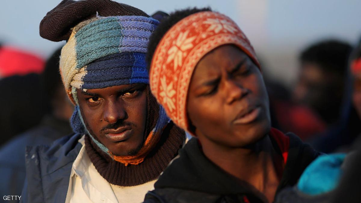 "CALAIS, FRANCE - OCTOBER 25:  Sudanese migrants queue in the cold weather to board buses and leave the notorious ""Jungle"" camp before authorities demolish the site on October 25, 2016 in Calais, France. Many migrants have left by coach to be reloctated at centres across France as Police and officials in France begin to clear the 'Jungle' migrant camp in Calais. Some 7,000 people are estimated to be living in the camp in squalid conditions.  (Photo by Christopher Furlong/Getty Images)"