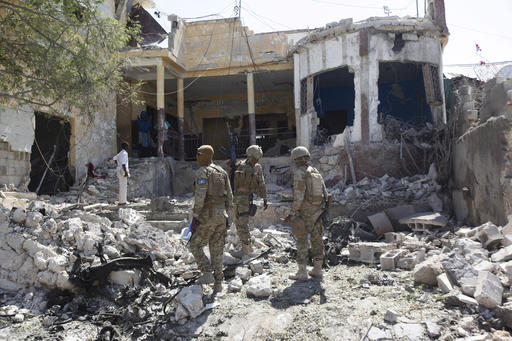 Somali soldiers stand in front of destroyed building near the scene of a suicide car bomb attack in Mogadishu, Somalia,Monday, Jan. 2, 2017. A suicide bomber detonated an explosives-laden vehicle at a security checkpoint near Mogadishu's international airport Monday, killing at least three people, a Somali police officer said. (AP Photo/Farah Abdi Warsameh)