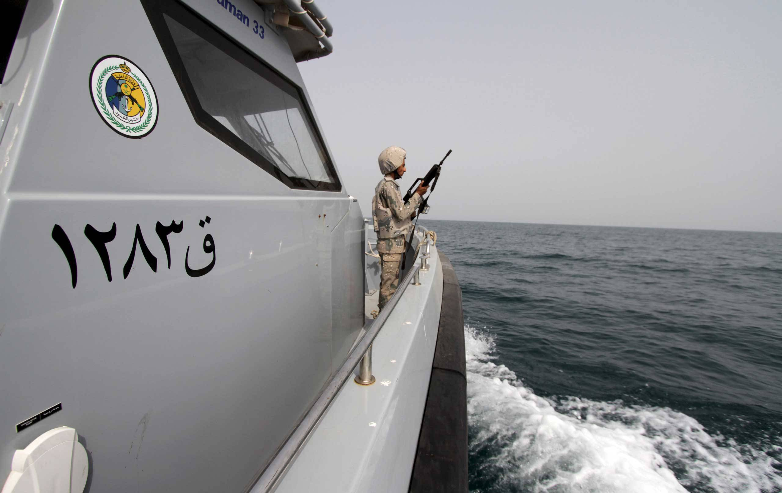 A Saudi border guard watches as he stands in a boat off the coast of the Red Sea on Saudi Arabia's maritime border with Yemen, near Jizan April 8, 2015. Iran sent two warships to the Gulf of Aden on Wednesday, state media reported, establishing a military presence off the coast of Yemen where Saudi Arabia is leading a bombing campaign to oust the Iran-allied Houthi movement. REUTERS/Faisal Al Nasser - RTR4WIGC