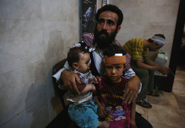 A Syrian man and two children await to receive treatment at a make-shift hospital in the rebel-held area of Douma, east of the capital Damascus, following reported air strikes by regime forces, on August 30, 2015. AFP PHOTO / ABD DOUMANY