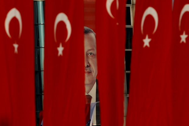 A picture of Turkish President Tayyip Erdogan is seen through Turkish national flags ahead of the constitutional referendum in Istanbul, Turkey, April 14, 2017.  REUTERS/Alkis Konstantinidis