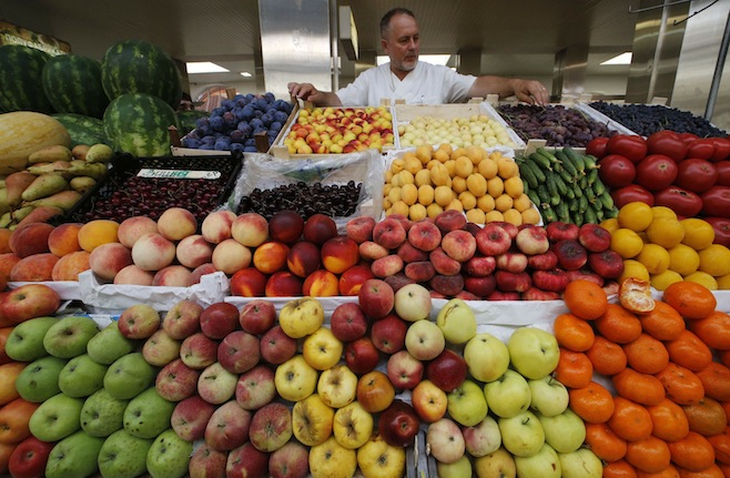A vendor sells vegetables and fruits at the city market in St.Petersburg August 7, 2014. Moscow imposed a total ban on imports of many Western foods on Thursday in retaliation against sanctions over Ukraine, a stronger than expected measure that isolates Russian consumers from world trade to a degree unseen since Soviet days. REUTERS/Alexander Demianchuk (RUSSIA - Tags: POLITICS AGRICULTURE FOOD BUSINESS TPX IMAGES OF THE DAY)