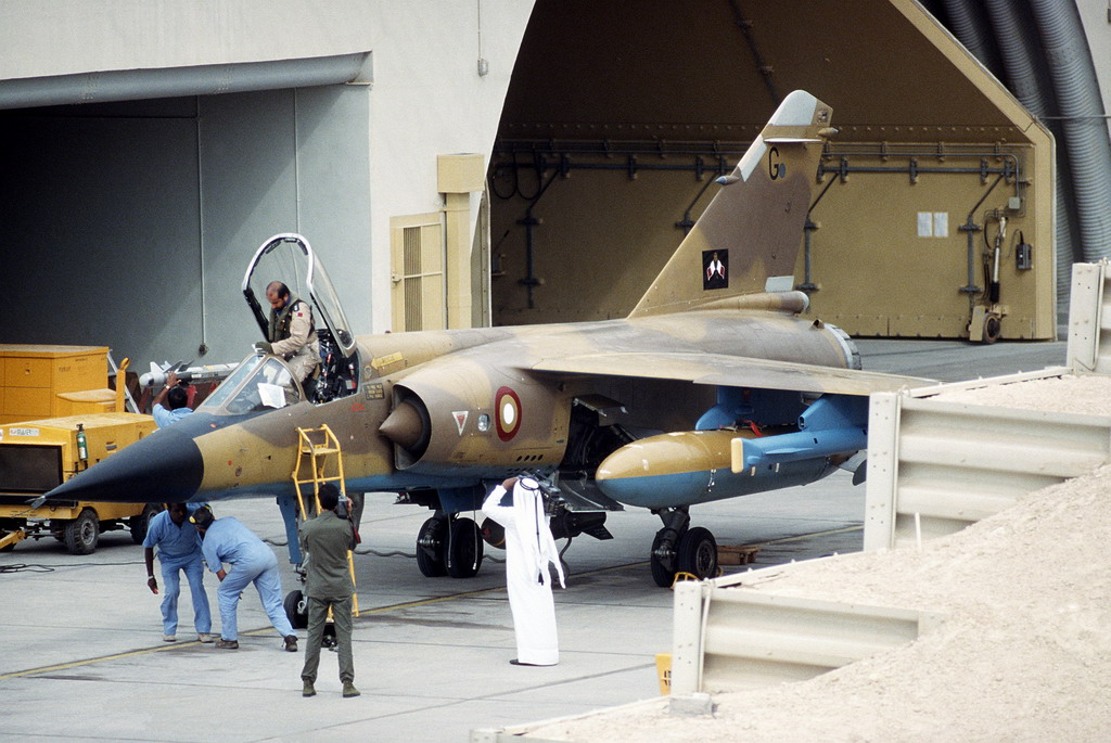 A pilot with the air force of Qatar performs a preflight check on his Mirage F1 aircraft prior to taking off on a mission during Operation Desert Storm.