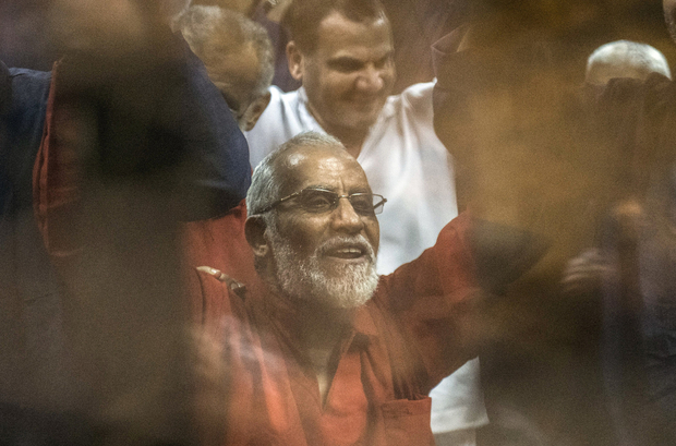 Egyptian Muslim Brotherhood leader Mohamed Badie (C) raises his hands from behind the defendant's cage as the judge reads out the verdict sentencing him and more than 100 other defendants, including Egypt's deposed Islamist president Mohamed Morsi, to death at the police academy in Cairo on May 16, 2015. AFP PHOTO / KHALED DESOUKI / AFP PHOTO / KHALED DESOUKI