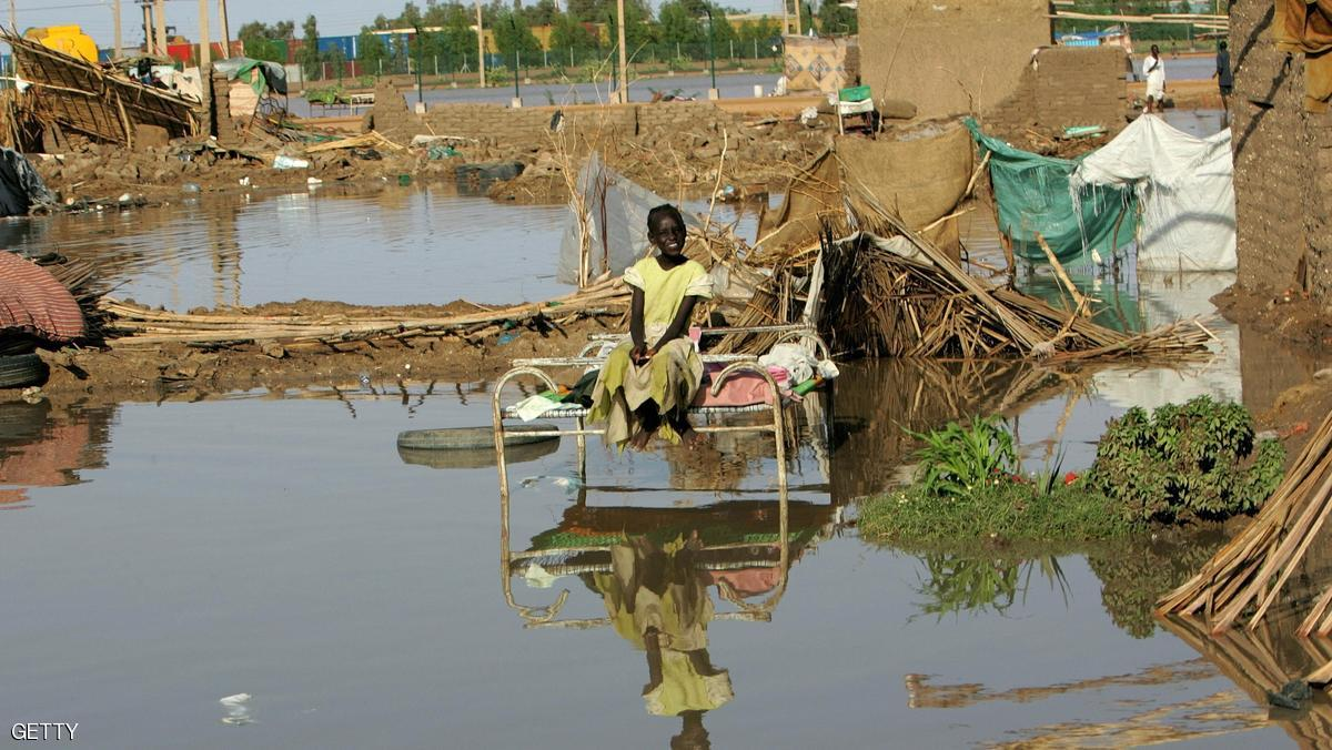 A Sudanese girl sits outside damaged mud huts following floods caused by heavy rain in southern Khartoum on August 29, 2009. AFP PHOTO/ASHRAF SHAZLY (Photo credit should read ASHRAF SHAZLY/AFP/Getty Images)