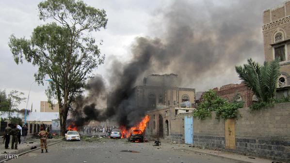 Smoke billows from burning cars as Yemeni security forces inspect the site of a car bomb attack targeting the convoy of the country's defence minister in Sanaa on September 11, 2012. Yemen's Defence Minister Mohammed Nasser Ahmed survived a car bomb attack that hit his convoy near the government headquarters, but 10 people were killed, including seven guards, a security official said. AFP PHOTO/GAMAL NOMAN        (Photo credit should read GAMAL NOMAN/AFP/GettyImages)