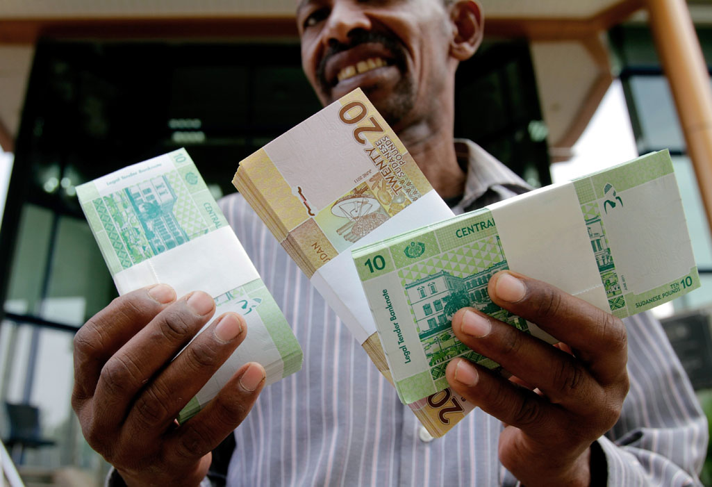 A Sudanese man shows freshly-minted notes of the new Sudanese pound in Khartoum on July 24, 2011 as the country issues new currency following the South's secession from the north.  AFP PHOTO/ASHRAF SHAZLY (Photo credit should read ASHRAF SHAZLY/AFP/Getty Images)
