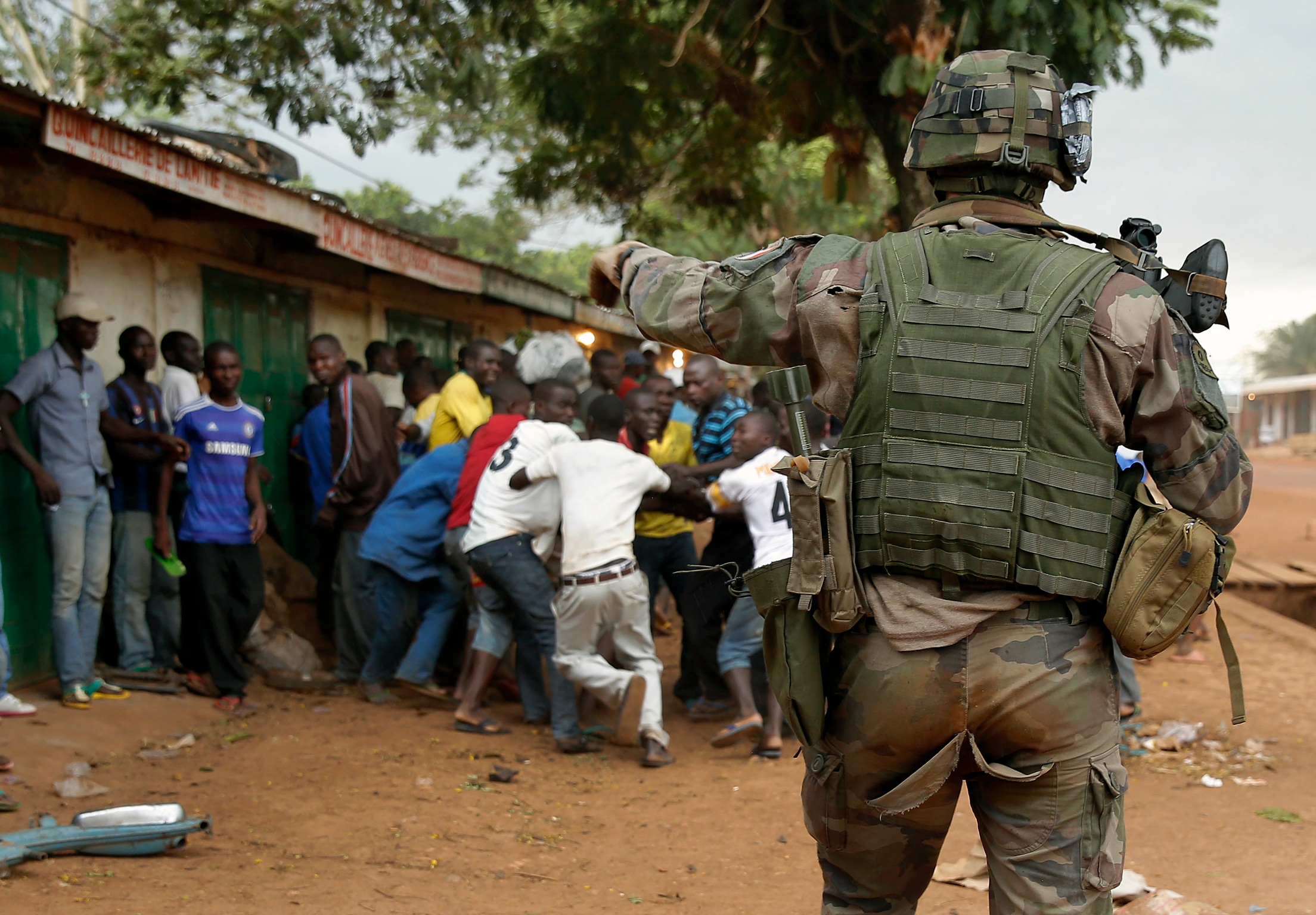 A French soldier screams at mobs of Christians attacking suspected Seleka members  before firing warning shots near the airport in  Bangui, Central African Republic, Monday  Dec. 9, 2013.  Both Christian and Muslim mobs went on lynching sprees as French Forces deploy in the capital. (AP Photo/Jerome Delay)