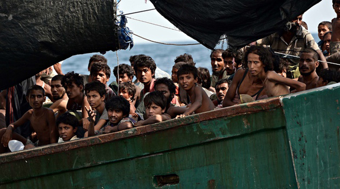 Rohingya migrants sit on a boat drifting