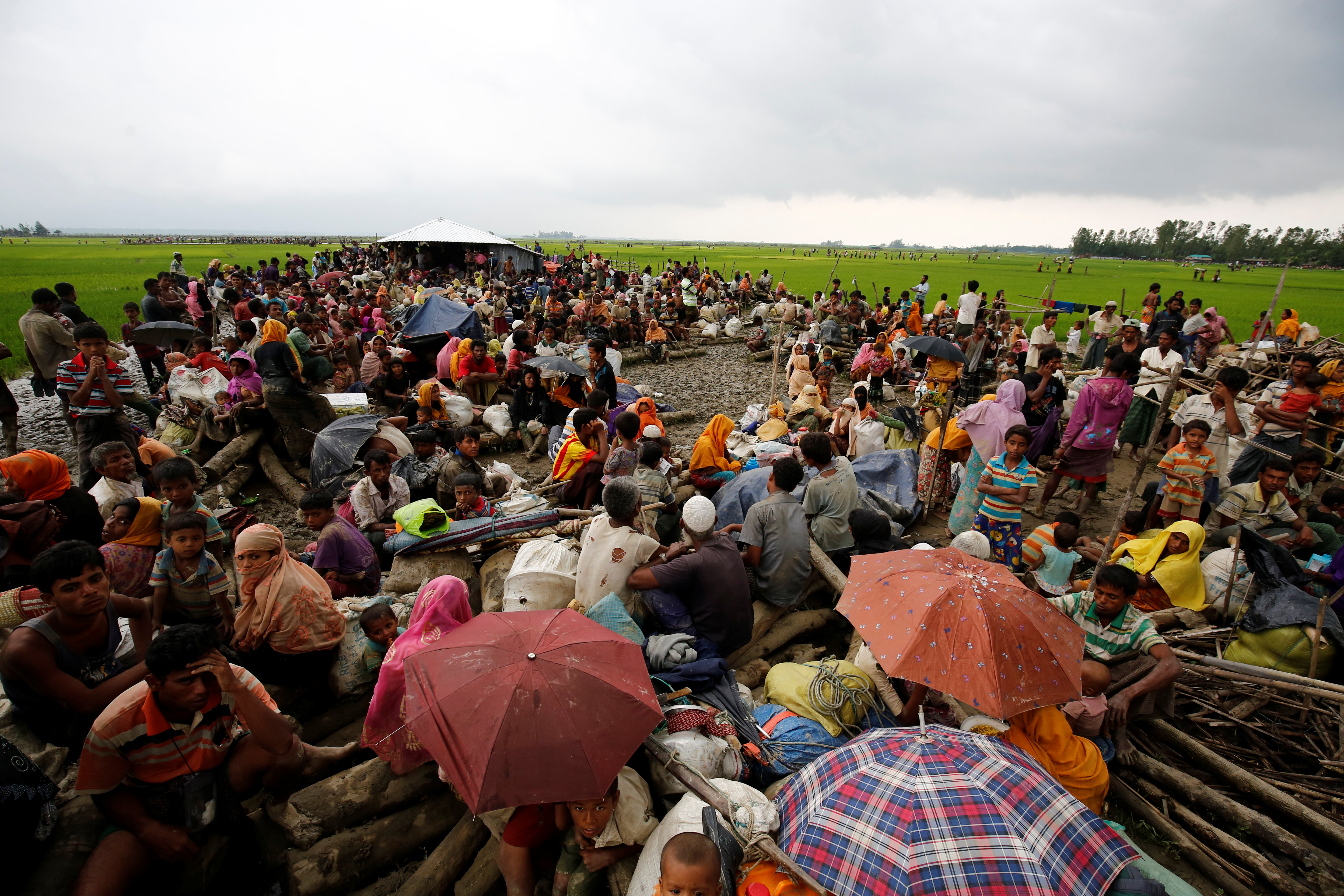Rohingya refugees sit as they are temporarily held by the Border Guard Bangladesh (BGB) in an open area after crossing the border, in Teknaf, Bangladesh, September 3, 2017. REUTERS/Mohammad Ponir Hossain