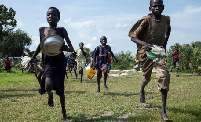 Children running in joy towards the humanitarian workers to secure food in South